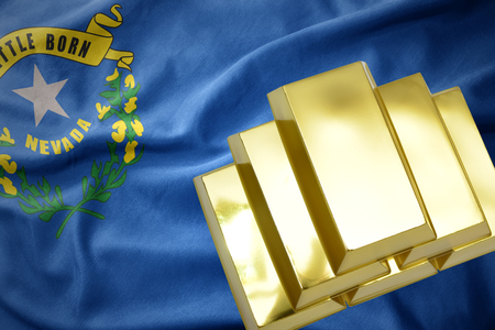 gold reserves. shining golden bullions on the nevada state flag background Stock Photo