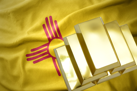 concern: gold reserves. shining golden bullions on the new mexico state flag background