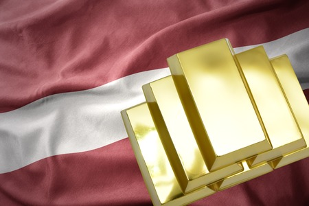 gold reserves. shining golden bullions on the latvia flag background