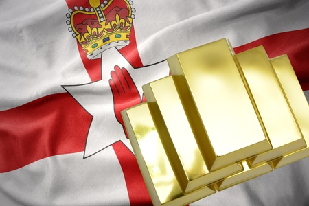 concerns: gold reserves. shining golden bullions on the northern ireland flag background.3D illustration Stock Photo