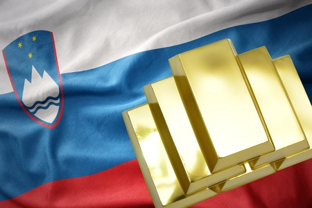 gold reserves. shining golden bullions on the slovenia flag background.3D illustration