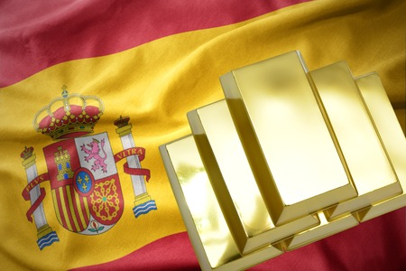 madrid spain: gold reserves. shining golden bullions on the spain flag background.3D illustration Stock Photo