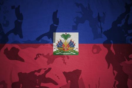 prince of peace: flag of haiti on the khaki texture background. military concept