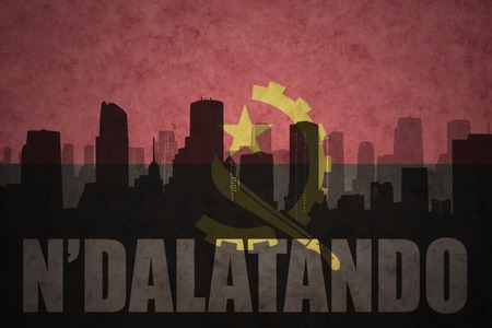abstract silhouette of the city with text Ndalatando at the vintage angolan flag background Stock Photo