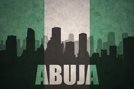 abstract silhouette of the city with text Abuja at the vintage nigerian flag background