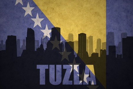 abstract silhouette of the city with text Tuzla at the vintage bosnian flag background