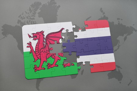 puzzle with the national flag of wales and thailand on a world map background. 3D illustration