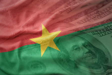 colorful waving national flag of burkina faso on a american dollar money background. finance concept