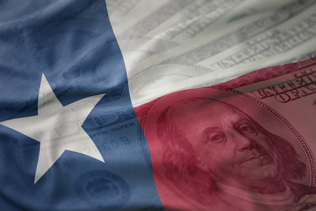 colorful waving flag of texas state on a american dollar money background. finance concept Stock Photo