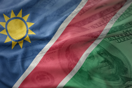 colorful waving national flag of namibia on a american dollar money background. finance concept