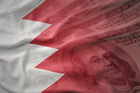 bahrain money: colorful waving national flag of bahrain on a american dollar money background. finance concept Stock Photo