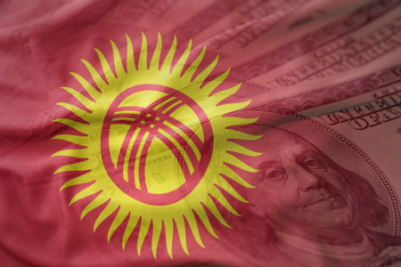 colorful waving national flag of kyrgyzstan on a american dollar money background. finance concept