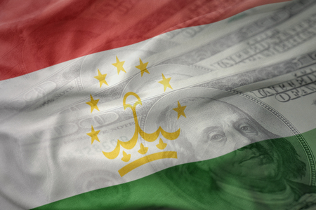 colorful waving national flag of tajikistan on a american dollar money background. finance concept