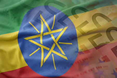 national flag ethiopia: colorful waving national flag of ethiopia on a euro money banknotes background. finance concept