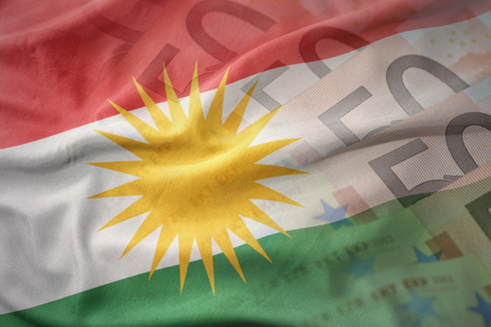 mideast: colorful waving national flag of kurdistan on a euro money banknotes background. finance concept