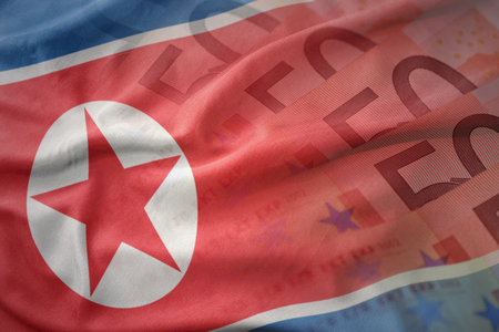 mideast: colorful waving national flag of north korea on a euro money banknotes background. finance concept