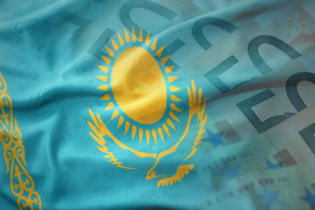 colorful waving national flag of kazakhstan on a euro money banknotes background. finance concept