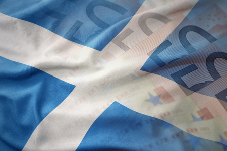 gb: colorful waving national flag of scotland on a euro money banknotes background. finance concept