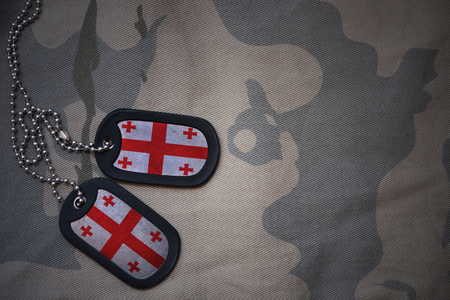 against the war: army blank, dog tag with flag of georgia on the khaki texture background. military concept Stock Photo