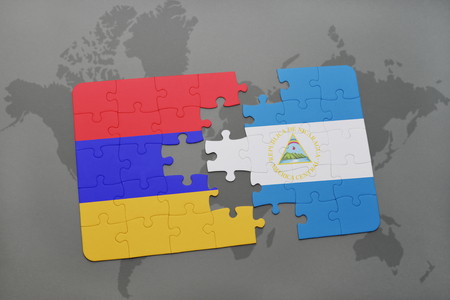 armenian: puzzle with the national flag of armenia and nicaragua on a world map background. 3D illustration