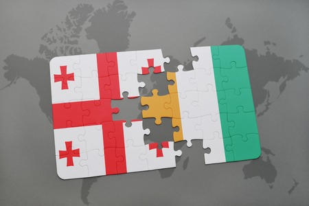 puzzle with the national flag of georgia and cote divoire on a world map background. 3D illustration