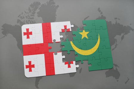 puzzle with the national flag of georgia and mauritania on a world map background. 3D illustration Stock Photo