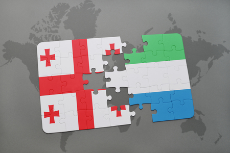 puzzle with the national flag of georgia and sierra leone on a world map background. 3D illustration