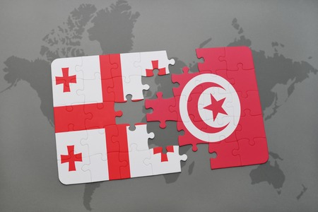 georgian: puzzle with the national flag of georgia and tunisia on a world map background. 3D illustration