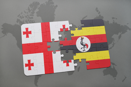 puzzle with the national flag of georgia and uganda on a world map background. 3D illustration