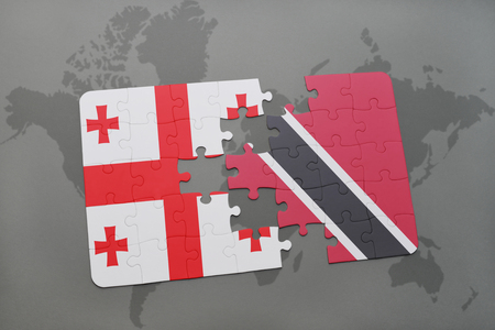 puzzle with the national flag of georgia and trinidad and tobago on a world map background. 3D illustration Stock Photo