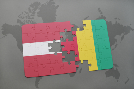 puzzle with the national flag of latvia and guinea on a world map background. 3D illustration