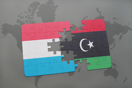 puzzle with the national flag of luxembourg and libya on a world map background. 3D illustration Stock Photo