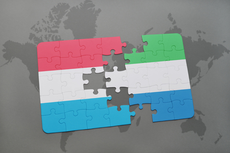 puzzle with the national flag of luxembourg and sierra leone on a world map background. 3D illustration