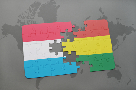 puzzle with the national flag of luxembourg and bolivia on a world map background. 3D illustration