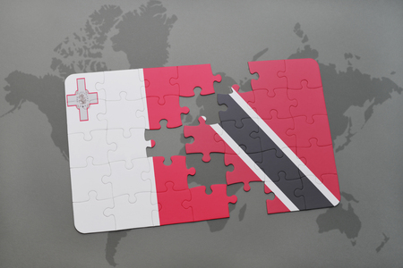 puzzle with the national flag of malta and trinidad and tobago on a world map background. 3D illustration Stock Photo