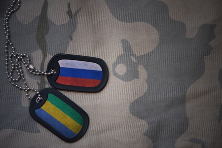 anti terrorist: army blank, dog tag with flag of russia and gabon on the khaki texture background. military concept Stock Photo