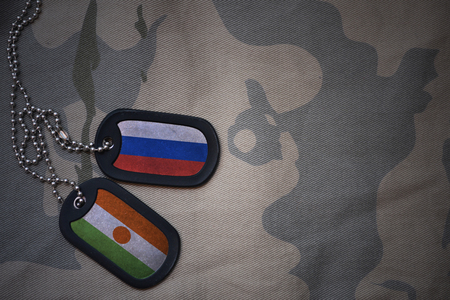 anti terrorist: army blank, dog tag with flag of russia and niger on the khaki texture background. military concept