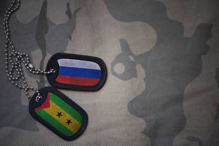 anti terrorist: army blank, dog tag with flag of russia and sao tome and principe on the khaki texture background. military concept Stock Photo