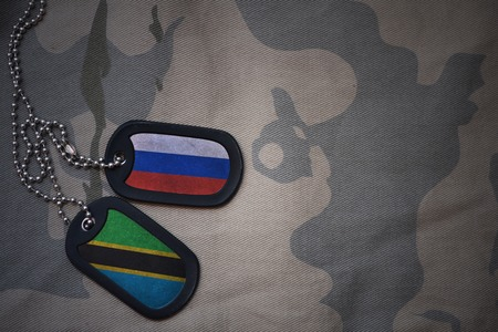 anti terrorist: army blank, dog tag with flag of russia and tanzania on the khaki texture background. military concept Stock Photo