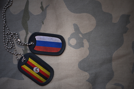 anti terrorist: army blank, dog tag with flag of russia and uganda on the khaki texture background. military concept Stock Photo