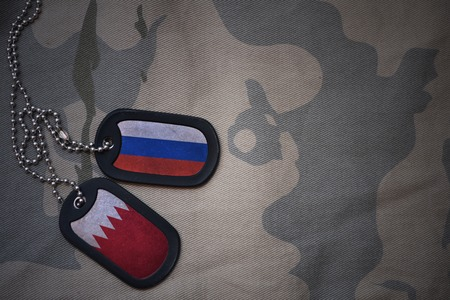 anti terrorist: army blank, dog tag with flag of russia and bahrain on the khaki texture background. military concept