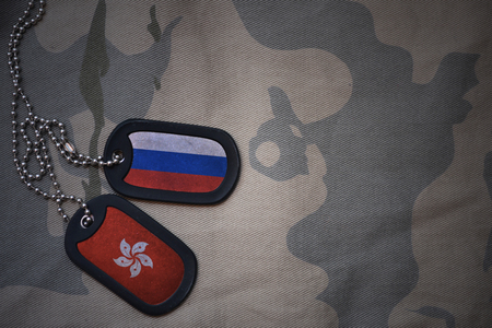 anti terrorist: army blank, dog tag with flag of russia and hong kong on the khaki texture background. military concept