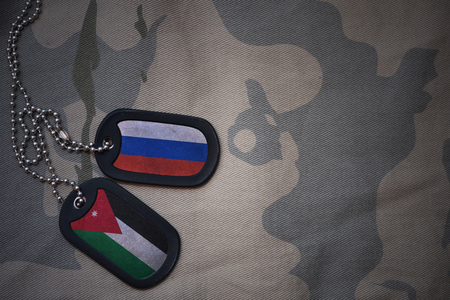 anti terrorist: army blank, dog tag with flag of russia and jordan on the khaki texture background. military concept