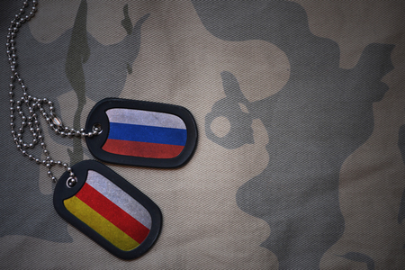 anti terrorist: army blank, dog tag with flag of russia and south ossetia on the khaki texture background. military concept