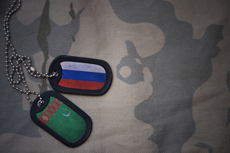 anti terrorist: army blank, dog tag with flag of russia and turkmenistan on the khaki texture background. military concept