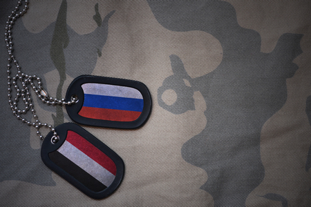 anti terrorist: army blank, dog tag with flag of russia and yemen on the khaki texture background. military concept
