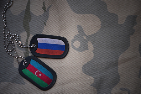 anti terrorist: army blank, dog tag with flag of russia and azerbaijan on the khaki texture background. military concept