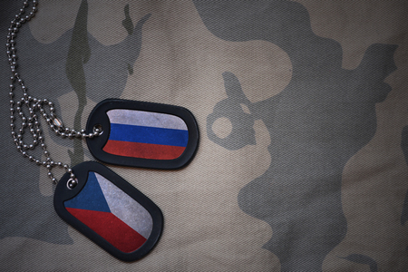anti terrorist: army blank, dog tag with flag of russia and czech republic on the khaki texture background. military concept