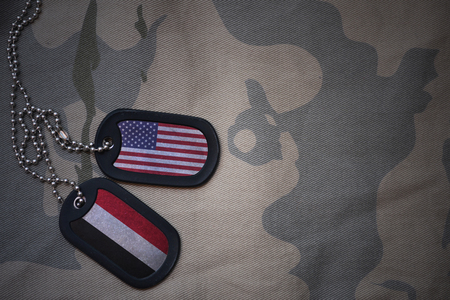 anti terrorist: army blank, dog tag with flag of united states of america and yemen on the khaki texture background. military concept