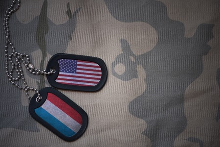 anti terrorist: army blank, dog tag with flag of united states of america and luxembourg on the khaki texture background. military concept